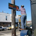 Joel standing on a mailbox taping a sign
